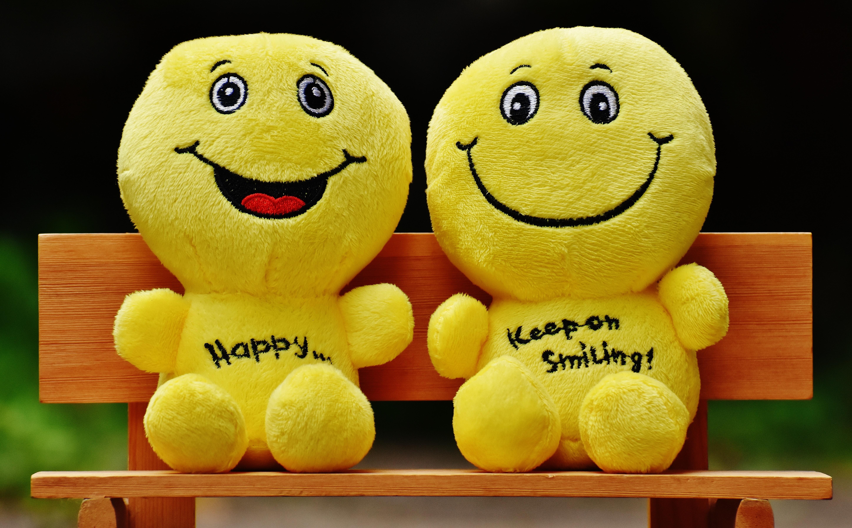 deux bonshommes en peluche jaune assis sur un banc